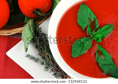 cold fresh diet tomato soup with basil thyme and dry pepper in big bowl over red mat on wood table ready to eat - stock photo