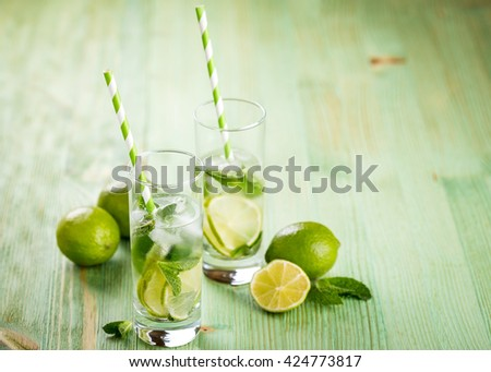 Cold fresh lemonade drink with lime and mint on a green wooden background - stock photo