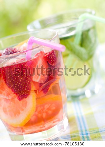 cold fresh lemonade drink with strawberry and lemon close up. Selective focus - stock photo