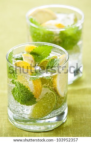 Cold fresh lemonade with lemon and lime on green background - stock photo