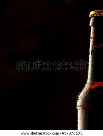 Cold frosted beer bottle border with a partial view of a sealed full bottle of lager or beer over a black background with copy space - stock photo