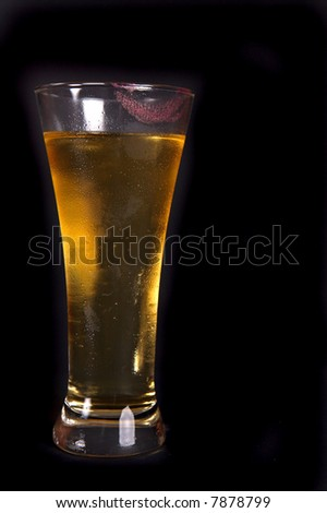 Cold glass of beer that has a drink taken out of it. With pink lipstick on the rim. - stock photo