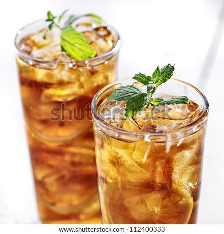 cold iced tea with mint garnish and sliced lemons - stock photo