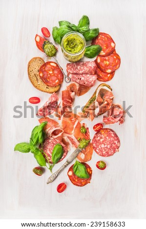 Cold  Italian meat plate with ham, sausage, bread and pesto on white wooden background, top view - stock photo