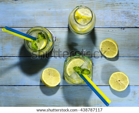 Cold lemonade in bottles with lemons on a blue wooden background. Top view - stock photo