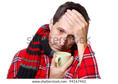 cold man with flu wrapped in a warm blanket, holding a mug - stock photo