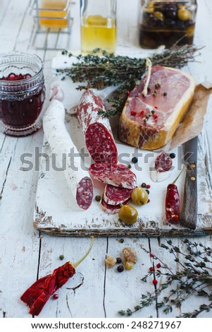 Cold meat plate of salchichon sausages and ham served with wine and red hot peppers on white wooden cutting board. See series. Natural meat concept.  - stock photo
