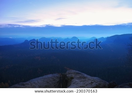 Cold misty blue morning. A minute before sunrise in a beautiful valley of rocky park. Sandstone peaks increased from blue fog.  - stock photo