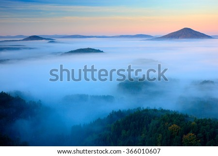 Cold misty foggy morning in a fall valley of Bohemian Switzerland park. Hills with fog, landscape of Czech Republic - stock photo
