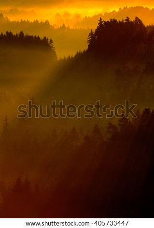 Cold misty foggy morning in a fall valley of Bohemian Switzerland park. Hills with fog, landscape of Czech Republic, sun beam in the landscape Ceske Svacarsko - stock photo