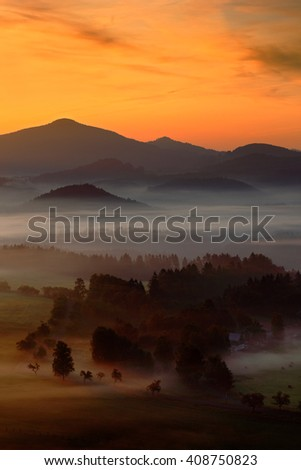 Cold misty foggy morning with sunrise in a fall valley of Bohemian Switzerland park. Hills with fog. Landscape of Czech Republic. Landscape in beautiful national park Ceske Svycarsko. - stock photo