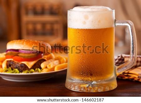cold mug of beer and hamburger - stock photo