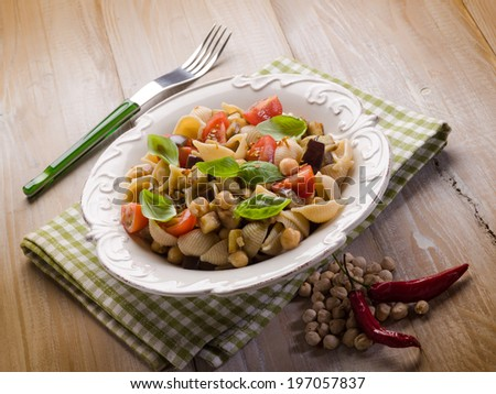 cold pasta salad with aubergine chickpeas and fresh tomatoes - stock photo