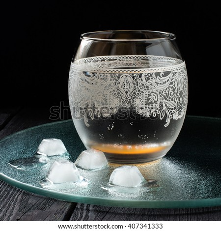 Cold pure mineral water in a beautiful glass with ornaments on the dark background. Square image  - stock photo