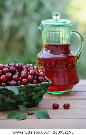 Cold refreshing drink from cherries in a pitcher and ripe berries in basket on wooden table in the garden - stock photo