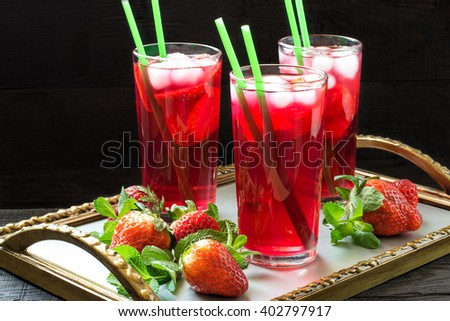 Cold refreshing drink with strawberries and ice in a glass of cocktail straws on a tray with fresh strawberries and mint - stock photo