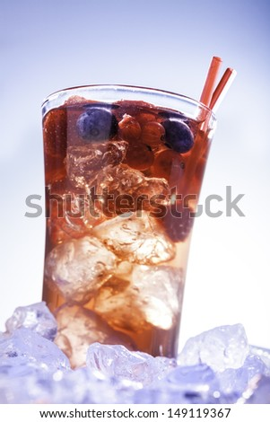cold refreshment with  berries, mint and soda on ice cubes  - stock photo