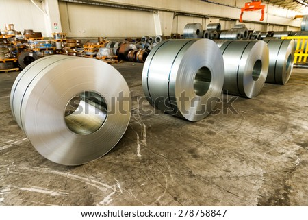 Cold rolled steel coils in storage area ready to feed to machine in metalwork manufacturing. - stock photo