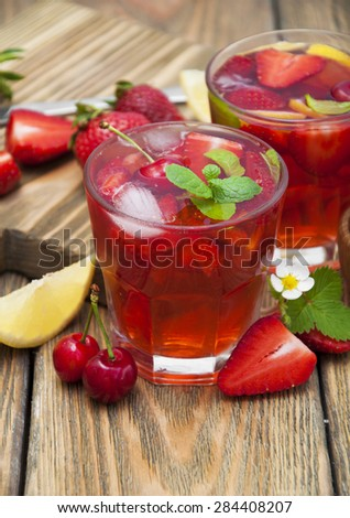 Cold strawberry and cherries drink with fresh strawberries,cherries and lemon on wooden background - stock photo