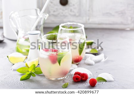 Cold summer refreshing cocktail with limes and raspberry - stock photo