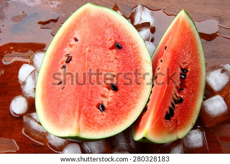 Cold watermelon on ice . watermelons slice on wood background. cool and juicy piece of watermelons. - stock photo