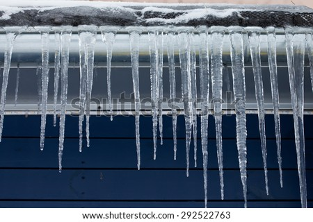 Cold weather concept. Icicles on the roof. Winter season. downspout. Blue wooden background. Cold time. Day. Soft focus - stock photo