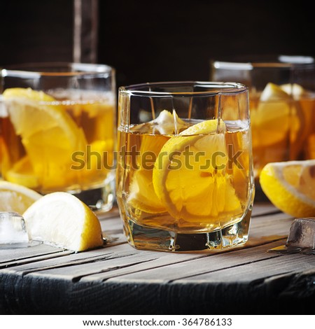 Cold whiskey with ice and lemon on the vintage table, selective focus and square image - stock photo