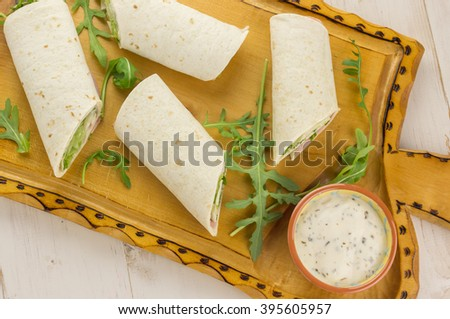 Cold wraps filled with ham and lettuce. Served with yogurt sauce on a wooden cutting board - stock photo