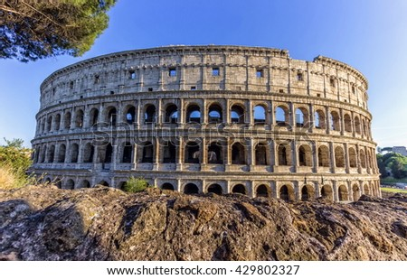 Coliseum behind rocks by day, Roma, Italy - stock photo