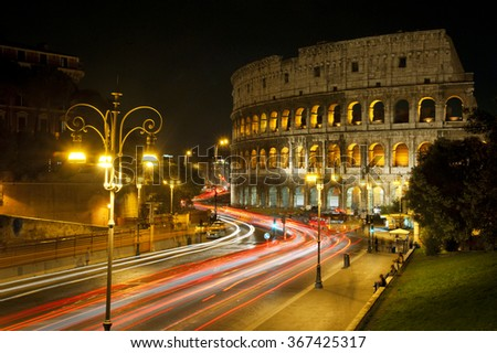 Coliseum in Rome at night and traffic light traces. - stock photo