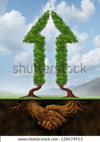 Collaborating for growth as a business agreement and cooperation concept in financial success as a group of partners working together as two arrow shaped trees with roots in the form of a hand shake. - stock photo