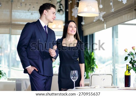 Collaborative romantic dinner in a restaurant. Young couple visits a restaurant. Woman is holding man's arm while the man sat down at the table and a woman looking out the window - stock photo