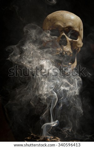 collage - ashtray and cigar smoke on the background of a human skull - stock photo