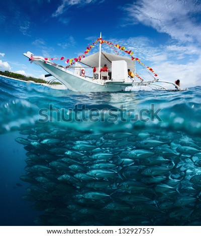 Collage with fishing boat on a surface and huge school of fish underwater. Philippines - stock photo