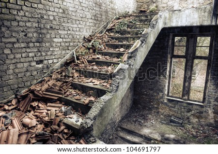 Collapsed roof tiles on a staircase in a derelict building - stock photo