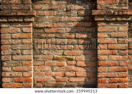 Collapsing stone wall of an old house with brick masonry - stock photo