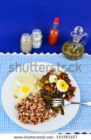 Collard greens seasoned with bacon drippings and salt pork and garnished with boiled egg on white plate with potato salad and black eyed peas.  Blue gingham setting adds to Southern or Country Feel. - stock photo