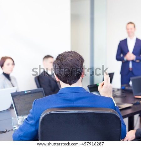 Colleague asking a question to  businessman during a presentation. Successful team leader and business owner  leading informal in-house business meeting. Business and entrepreneurship concept. - stock photo