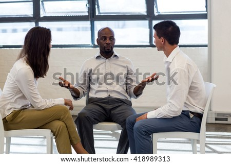 Colleague making hand gesture during a meeting in office - stock photo
