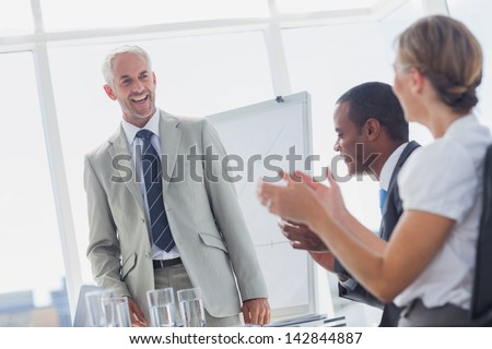 Colleagues applauding smiling manager during a meeting in a meeting room - stock photo