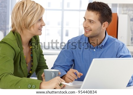 Colleagues chatting, sitting together at office table, smiling.? - stock photo