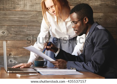 Colleagues discussing documents sitting in the office. African executive officer holding papers, explaining business plans for his redhead assistant, who is listening attentively, standing next to him - stock photo