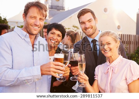 Colleagues drinking after work at a rooftop bar - stock photo
