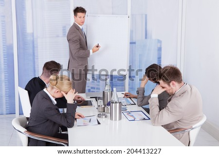 Colleagues getting bored during business presentation given by businessman in office - stock photo