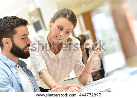 Colleagues in office checking agenda - stock photo