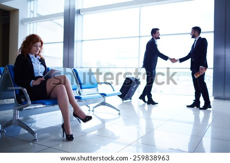 Colleagues meeting in the airport - stock photo
