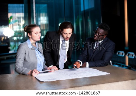 Colleagues reviewing their project together in office. - stock photo