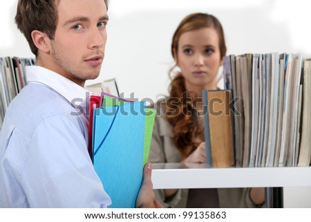 Colleagues surrounded by file folders - stock photo