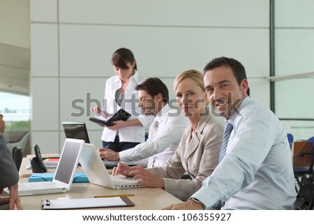 Colleagues working at laptop computers in an office environment - stock photo