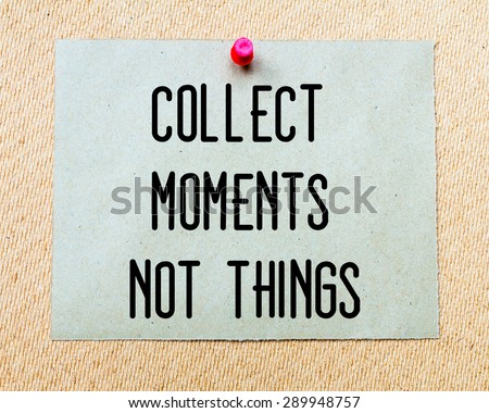 Collect Moments Not Things  written on paper note pinned with red thumbtack on wooden board. Motivation conceptual Image - stock photo